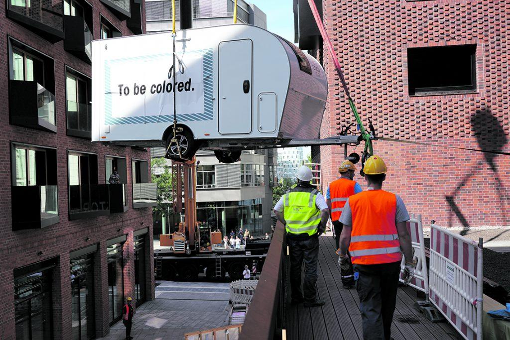 """Einer von drei Pierdrei-Wohnwagen schwebt in die """"Camper City"""" auf die Terrasse im 1. OG des neuen Pierdrei-Hotels ein. Foto: Thomas Hampel"""
