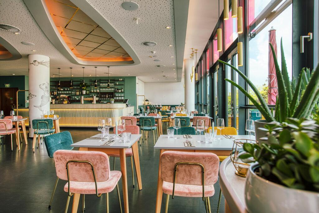 """""""Reep""""-Restaurant: Das Interieur orientiert sich an den 1950ern, jedoch in einer modernen Version. Die schlichten Stühle sind mit gelben, rosa oder blauen Stoffen bezogen, eine Wand wurde in einem warmen Grünton gestrichen. © Brinkhoff / Mögenburg"""