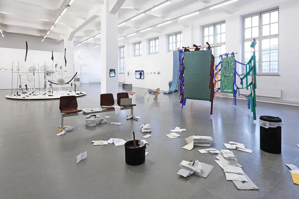 """Mit seiner Installation """"No fear of sleep"""" greift Jáno Möckel das Thema verdrängte Schulden auf. Darum hat er Briefe, durch die Logos von Firmen und Kreditinstituten hindurchscheinen, um eine Traversenbank arrangiert. © Nominees, Installationsansicht, Kunsthaus Hamburg 2021, Foto: Hayo Heye"""