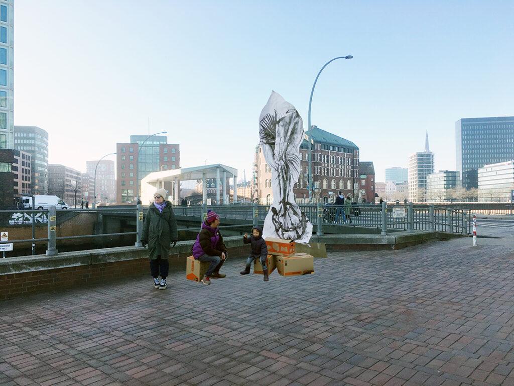 """Die Skulptur """"One More Try"""" der deutschen Künstlerin Franziska Nast vor dem HafenCity-Eingang an der Oberbaumbrücke wie die anderen Werke des Kunstspaziergangs """"The Gate"""" zeigt die HafenCity als einen sich """"ständig wandelnden Organismus, in dem Gebäude und Menschen sich wechselseitig beeinflussen. Die fünf übergreifenden Kapitel Kontrolle, Limbo, Paradies, Potenz und Übersee verbinden eine lokal verortete Audiothek und einen Kunst-parcours, der in 16 Stationen durch die HafenCity"""" führt. © Visualisierung:  Franziska Nast, ONE MORE TRY, Oberbaumbrücke, © Franziska Nast"""