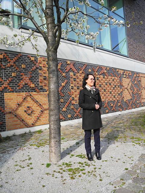 """Feng-Shui-Analystin Tu Phung Ngo vor den sand- und terrakottafarbenen Häuserwharften: """"Sehen Sie die Verzierungen, wie Mosaike. Das ist Liebe zum Detail."""" © Katrin Wienefeld"""