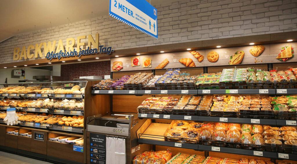 """Die große Backwarenauslage ist mit einem rückgelagerten Backraum versehen, sodass die Mitarbeiter des Marktes die Regale bequem von der Rückseite befüllen können. """"Hier können sich unsere Kunden zudem künftig über ein vergrößertes Sortiment an verschiedenen Brot- und Backwaren freuen, darunter auch süße Teilchen und herzhafte Snacks"""", erläutert ALDI-Filialleiter Tomas Krzystek. © ALDI Nord"""